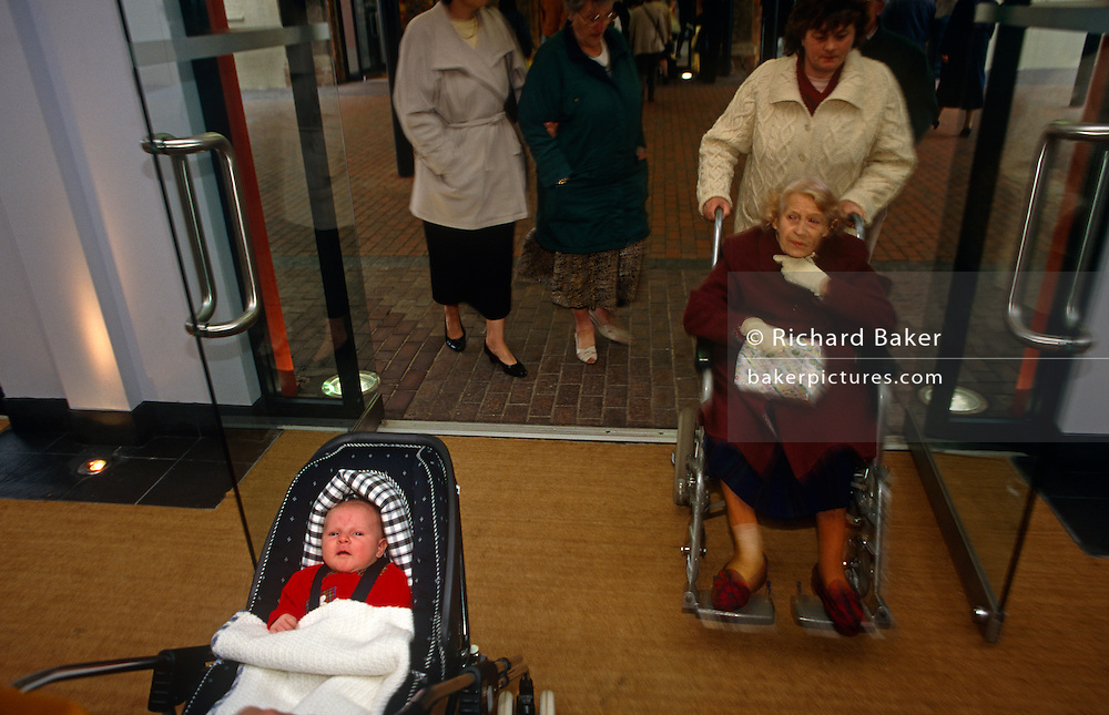 Generation gap: As an elderly lady enters a department store in her wheelchair, so a young baby is pushed in its buggy