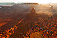East, West and Merrick Buttes in Monument Valley backlit by the setting sun