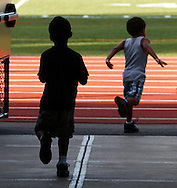 Two boys run toward the track at Middletown High School during the Twilight Track and Field Series on Tuesday, July 30, 2013.