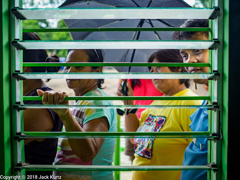 29 JANUARY 2018 - GUINOBATAN, ALBAY, PHILIPPINES: Evacuees from Mayon volcano wait to pick up emergency supplies at the shelter in Mauraro National High School in Guinobatan. There are 1,773 people in the shelter. Mayon volcano's eruptions continued Monday. At last count, more 80,000 people have been evacuated from their homes of the slopes of the volcano and are crowded into shelters in communities outside of the danger zone.    PHOTO BY JACK KURTZ