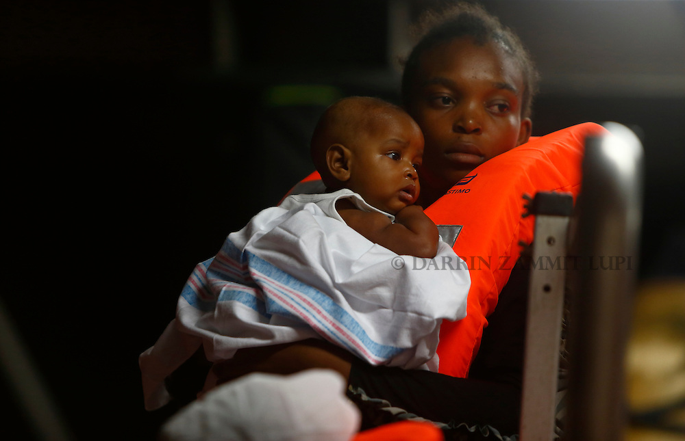 A migrant carries her baby on the Migrant Offshore Aid Station (MOAS) ship MV Phoenix while waiting to be transferred to the Norwegian ship Siem Pilot off the coast of Libya August 6, 2015.  An estimated 700 migrants on an overloaded wooden boat were rescued 10.5 miles (16 kilometres) off the coast of Libya by the international non-governmental organisations Medecins san Frontiere (MSF) and MOAS without loss of life on Thursday afternoon, according to MSF and MOAS, a day after more than 200 migrants are feared to have drowned in the latest Mediterranean boat tragedy after rescuers saved over 370 people from a capsized boat thought to be carrying 600.<br /> REUTERS/Darrin Zammit Lupi <br /> MALTA OUT. NO COMMERCIAL OR EDITORIAL SALES IN MALTA