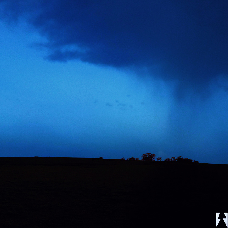Left triptych panel of a panorama photo of a field swept by blue hues of rain as seen from afar.