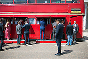 © Licensed to London News Pictures. 06/06/2014. Epsom, UK. People at a bar converted from a red bus.  Ladies Day today 6th June 2012 at Epsom 2014 Investic Derby Festival in Surrey. Traditionally, elegant, fashionable racegoers gather for a classic day's racing at Epsom Racecourse, Surrey. Photo credit : Stephen Simpson/LNP