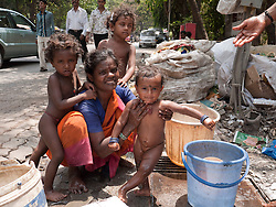 Woman with buckets of water bathing children outside shanty shack in Mumbai.
