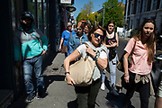 People walking away from Portobello Road Market in Notting Hill, West London, England, United Kingdom. People enjoying a sunny day out hanging out at the famous Sunday market, when the antique stalls line the street.  Portobello Market is the worlds largest antiques market with over 1,000 dealers selling every kind of antique and collectible. Visitors flock from all over the world to walk along one of Londons best loved streets.
