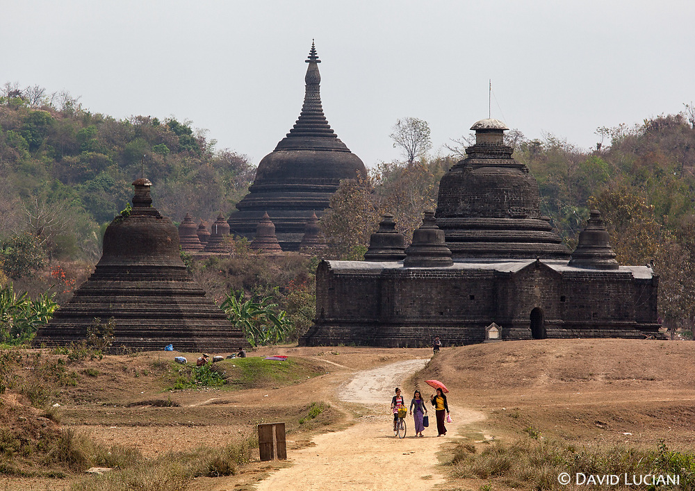 Three young ladies walking in the midday sun leaving Ratanabon Pagoda and Htukkanthein Temple behind their.