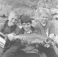 Three young loons (boys) with a slamon caught in a bag net by local salmon netters at Boddin, Angus.<br /> Ref. Catching the Tide 51/00/08 (2nd August 2000)<br /> <br /> The once-thriving Scottish salmon netting industry fell into decline in the 1970s and 1980s when the numbers of fish caught reduced due to environmental and economic reasons. In 2016, a three-year ban was imposed by the Scottish Government on the advice of scientists to try to boost dwindling stocks which anglers and conservationists blamed on netsmen.