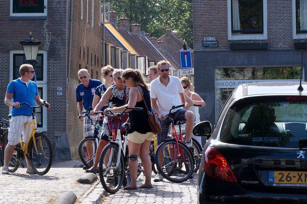 In Utrecht moet een automobilist  zich langs een groep fietsers wringen die de fietsroute van Colorbike Tours aan het doen zijn.<br /> <br /> In Utrecht a car driver has to manouvre his car past a group cyclists who are riding the city tour by Colorbike Tours.