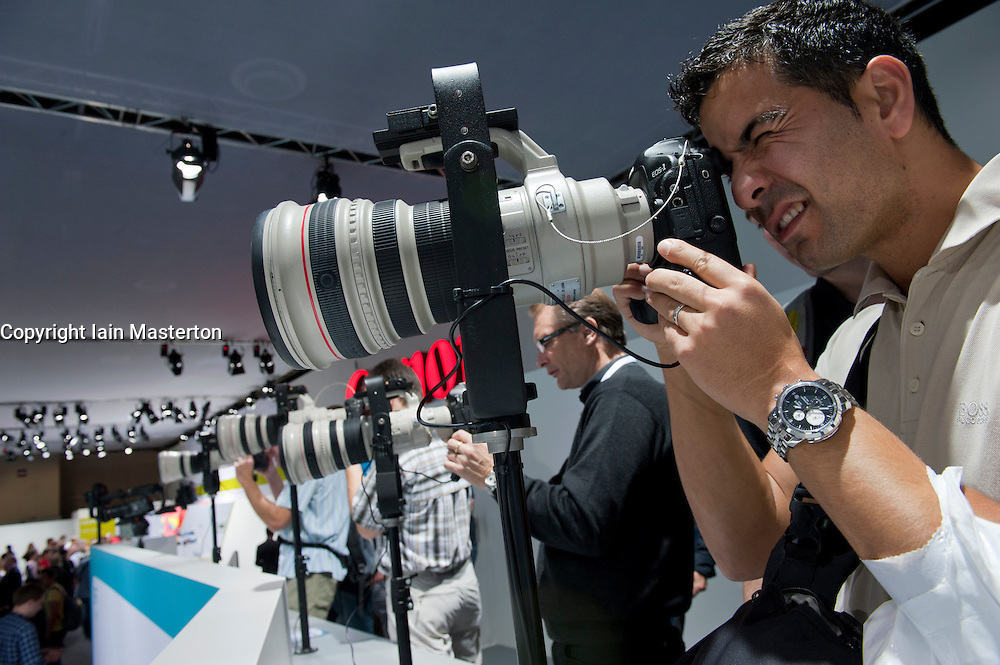 Visitor using Canon telephoto lens and camera at Photokina digital imaging trade show in Cologne Germany 2010