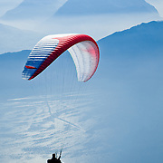 A man paragliding in the Swiss Alps near Mount Rigi.<br /> <br /> + ART PRINTS +<br /> To order prints or cards of this image, visit:<br /> http://greg-stechishin.artistwebsites.com/featured/paragliding-2-greg-stechishin.html
