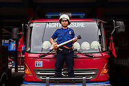Fire fighter posing with truck and gear in Jakarta, Indonesia.