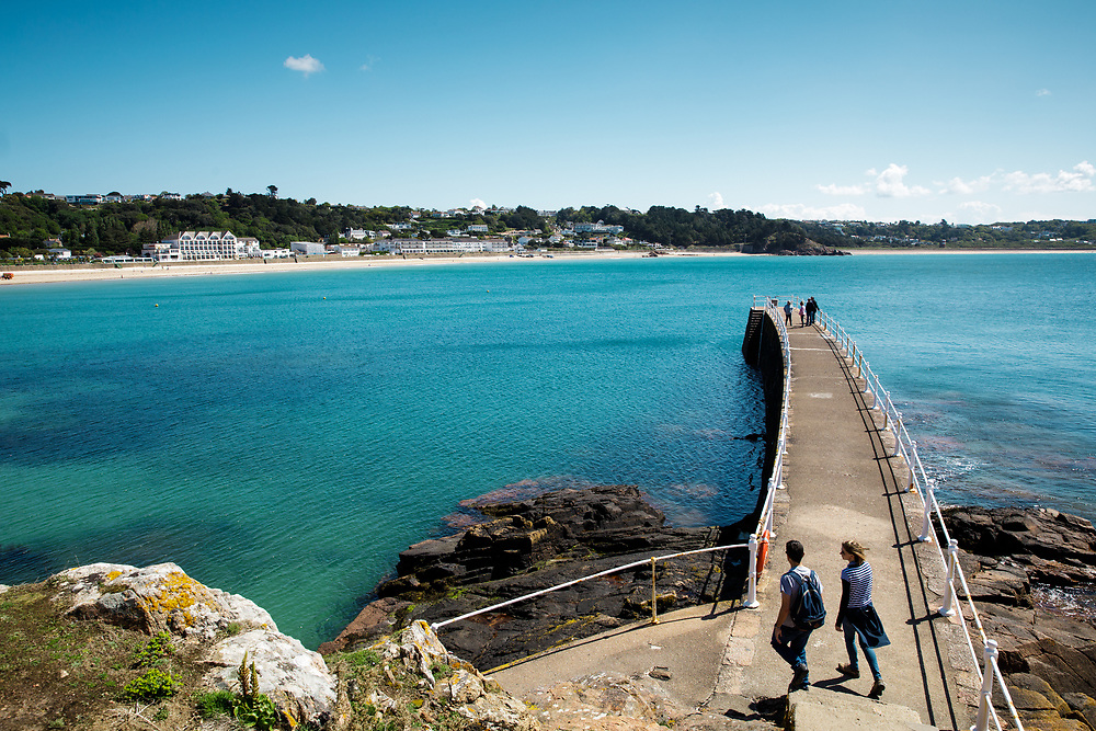 Calm, turquoise water surrounding the pier at St Brelade's Bay, a popular beach with tourists in Jersey, Channel Islands