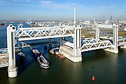 Nederland, Zuid-Holland, Rotterdam, 18-02-2015; bouw van de nieuwe Botlekbrug, binnenvaartschip passeert de nieuwe brug. De brug over de Oude Maas is een hefbrug, een van de twee brugdelen in geheven toestand. De heftorens van de oude brug gaan verscholen achter de nieuwe brug. <br /> Construction of the new Botlek bridge. The bridge over the Oude Maas is a vertical-lift bridge or lift bridge, one of the two bridge sections raised. <br /> luchtfoto (toeslag op standard tarieven);<br /> aerial photo (additional fee required);<br /> copyright foto/photo Siebe Swart