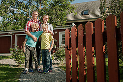 Young family standing garden gate new home