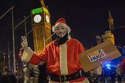 London, November 5th 2016. Anti-capitalists and anarchists participate in the Million Mask March, an annual event that happens on November 5th each year in cities across the world, as part of a protest against the establishment. Many of the protesters wear Guy Fawkes masks, often associated with the internet activism group Anonymous. PICTURED: A protester dressed as Father Christmas offers free hugs in Parliament Square.
