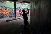 Sinister graffiti artist silhouette sprays walls in underpass tunnel in Waterloo.