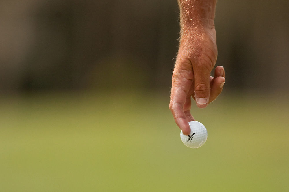 Close-up of fingers and Bridgestone golf ball being removed from cup by Charles Howell III during round 4 of the 2010 Verizon Heritage Classic. Photographed at Harbour Town Golf Links on Hilton Head Island, South Carolina on Sunday, April 18, 2010. Photograph © 2010 Darren Carroll
