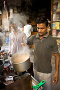 A Chai Wallah or tea maker makes tea in Old Delhi, India.<br /> Tradionally Indian tea is a mixture of tea leaves, water, sugar and sometimes spices boiled together and strained into cups