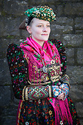 Isabell of the Volkstrachtenverein Ochsenfurt e.V.  is wearing an original traditional costume in Ochsenfurt, Lower Franconia, Germany on February 18, 2018.<br /> <br /> The original dress is from around 1920 and was worn during the Corpus Christi celebrations when the 'Marienbild-Mädchen' carrying the Figure of the Virgin Mary in front of the procession.<br /> The shoes are called Kommodschuhe (aka comfortable shoes) and are original - they don't have left or right feet.