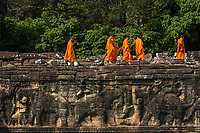 Monks walking on the Terrace of the Elephants, Angkor Thom,Cambodia. It was built in the late-12th century as a viewing platform, from which King Jayavarman VII looked over his victorious returning army.