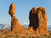 Balanced Rock catches golden rays of sunset in Arches National Park, Utah, USA. The Entrada Sandstone at Balanced Rock (128 feet/39 meters high) mounts a caprock of the hard Slick Rock Member upon a base of the Dewey Bridge Member, a mudstone. The snow-dusted La Sal Mountains reach 12,780 feet in elevation, formed as a result of intrusion of igneous rocks and subsequent erosion of the surrounding less-resistant sedimentary rocks.