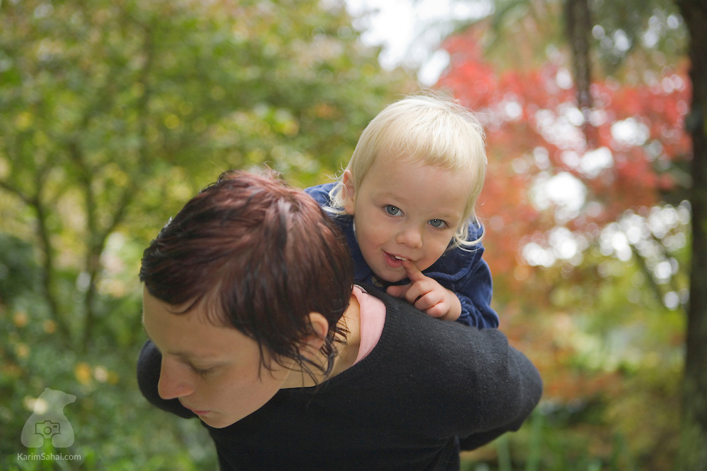 A mother and her young boy hang out in a garden, during autumn.