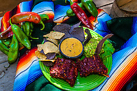 Fiesta platter (chile con queso, guacamole, red chile ribs and tortilla chips) with red and green chiles in background, El Pinto Restaurant and Cantina, Albuquerque, New Mexico USA