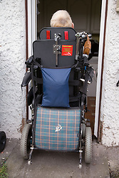 Woman with Cerebral Palsy in a electric wheel chair entering her house,