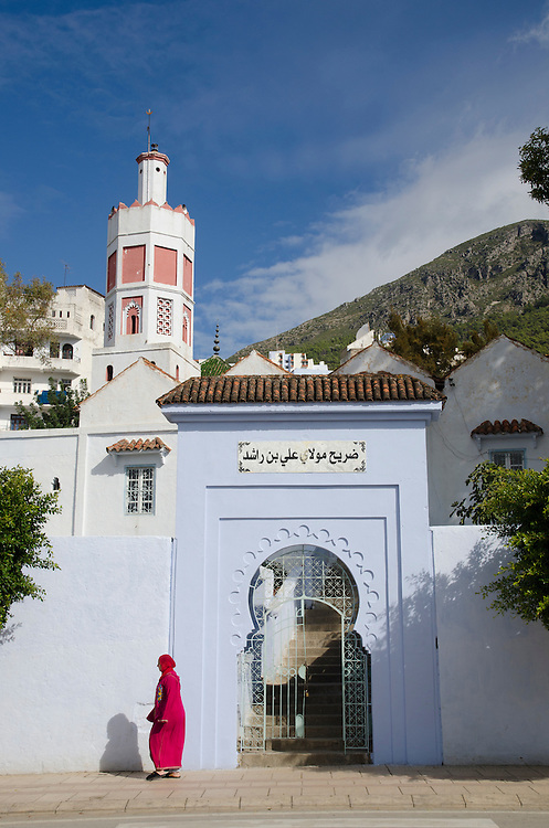 An Arab woman walks past mosque in Chefchaouen, Morocco