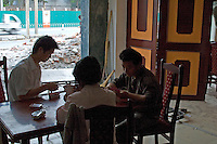 China, Beijing, Chaoyang, San Jian Fang, 2008. Halfway between the destruction of the old and the opening of the new, idled restaurant workers along Chaoyang Street while away the afternoon with a card game.