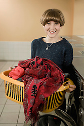 Young woman with laundry, smiling