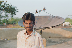 Indian cable operator affected by polio; member of selfhelp group supported by charity ADD India; standing in front of satellite dish,