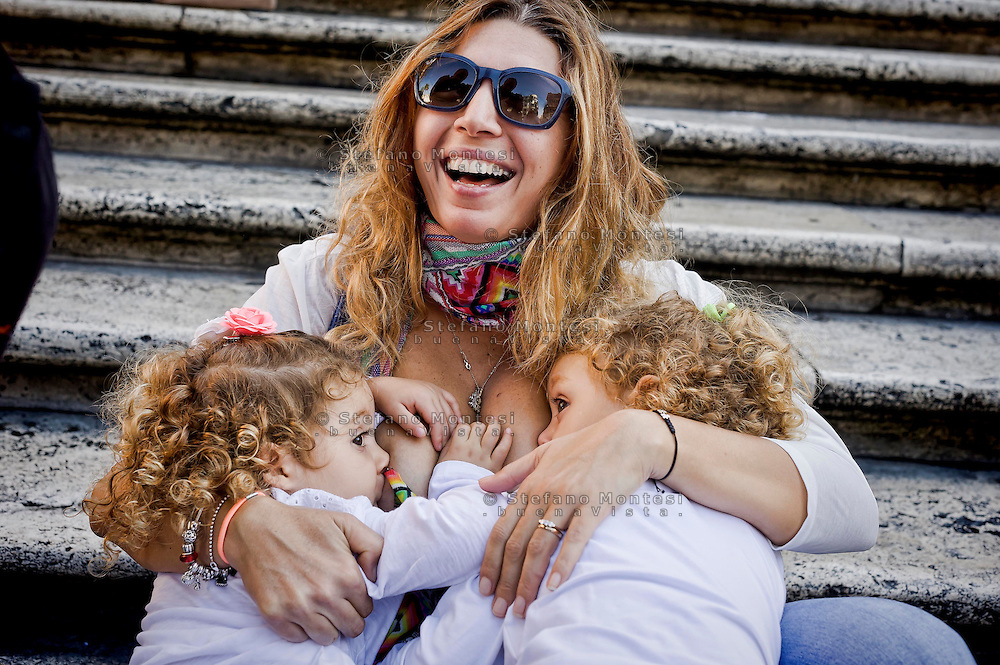ROME, ITALY - OCTOBER 3: Mom breast feeding children, the Trinita dei Monti, during the World Week for the breastfeeding, organized  by the Movement Lactation Maternal Italian with the aim of promoting the benefits of breastfeeding on October 3, 2015 in Rome, Italy.