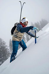 Male mountain climber going up snowy slope with pick axe, Zell Am See, Austria