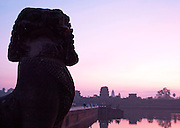 A statue by the crossing to Angkor Wat at sunrise, Siem Reap Province, Cambodia