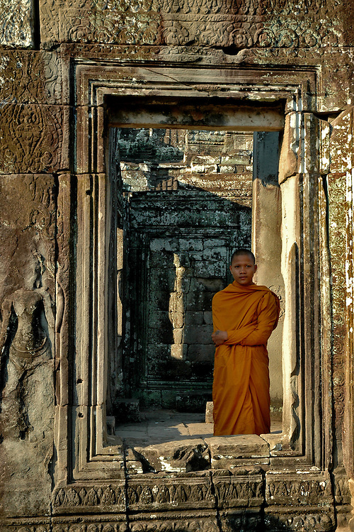 This image of a Cambodian Buddhist Monk was shot at the Bayon temple Ta Prohm in Angkor Thom city.<br /> <br /> The Bayon is the second most well known temple after Angkor Wat in the Angkor complex located at the center of Angkor Thom city.  The ruins of Angkor, a UNESCO World Heritage Site with temples numbering over one thousand, are hidden amongst forests and farmland to the north of the Tonle Sap Lake (Great Lake) and south of the Kulen Hills outside the modern city of Siem Reap, Cambodia.  Angkor served as the seat of the Khmer empire and flourished from approximately the 9th century to the 13th century. <br /> <br /> Built in the late 12th or early 13th century as the official state temple of King Jayavarman VII,  the Bayon temple is comprised of <br /> 54 towers with the smiling face of Avalokiteshvara.<br /> <br /> These Buddhist Saints or bodhisattva embody the compassion of all Buddhas and are a beautiful and powerful sight to behold. Exploring the Bayon was an amazing experience.