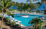 photographie publicitaire en couleur de la piscine de l'hôtel Le Méridien Nouméa situé en Nouvelle Calédonie sur laquelle apparait une magnifique piscine entourée de parasols, de transat avec la mer en arrière plan.