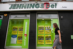 © Licensed to London News Pictures. 14/06/2020. London, UK. A woman walks past a branch of Jennings Bet in north London which will reopen on 15 June as coronavirus lockdown restrictions are eased. <br /> The government has announced that all betting shops can re-open on Monday 15 June. Betting shops were closed late March following outbreak of COVID-19. Photo credit: Dinendra Haria/LNP