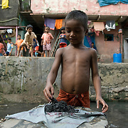 A boy playing with black mud he dug out of the 'dhobi talab', the water tank where the cloths washing cast (Dhobi wala) do the community's laundry.