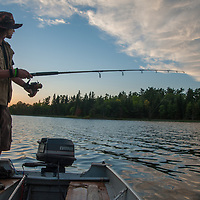 Ben Wiltsie rides fishes from an outboard motor boat on Lake of the Woods, Ontario, Canada.