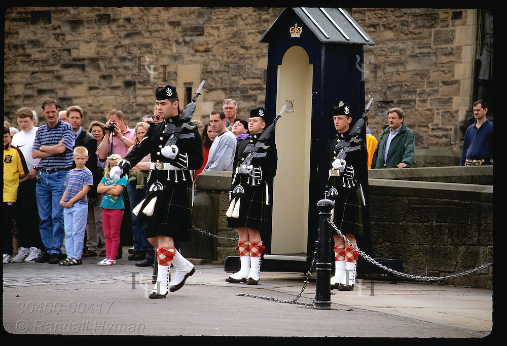 Tourists watch as soldiers march from guardhouse during changing of guard at Edinburgh Castle. Scotland