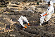 02 AUGUST 2013 - KOH SAMET, RAYONG, THAILAND: Workers cleanup an oil spill on the rocks of Ao Prao Beach on Koh Samet island. About 50,000 liters of crude oil poured out of a pipeline in the Gulf of Thailand over the weekend authorities said. The oil made landfall on the white sand beaches of Ao Prao, on Koh Samet, a popular tourist destination in Rayong province about 2.5 hours southeast of Bangkok. Workers from PTT Global, owner of the pipeline, up to 500 Thai military personnel and volunteers are cleaning up the beaches. Tourists staying near the spill, which fouled Ao Prao beach, were evacuated to hotels on the east side of the island, which was not impacted by the spill. Officials have not said when Ao Prao beach would reopen. PTT Global Chemical Pcl is part of state-controlled PTT Pcl, Thailand's biggest energy firm.    PHOTO BY JACK KURTZ