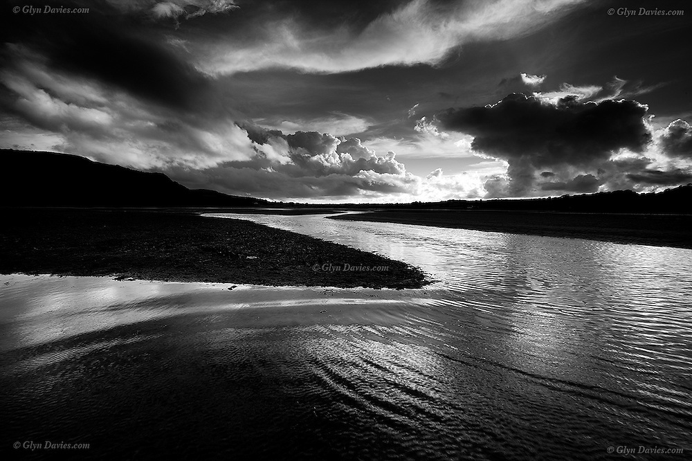 Ripples on deep water channels left between sand banks and mud flats at low tide in the Dulas Estuary near Lligwy, East Anglesey, in showery weather, with dramatic clouds in the sky.