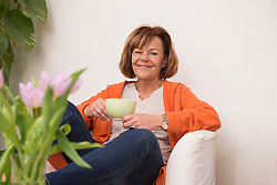 Happy senior woman sitting on sofa and having cup of tea at home, Munich, Bavaria, Germany