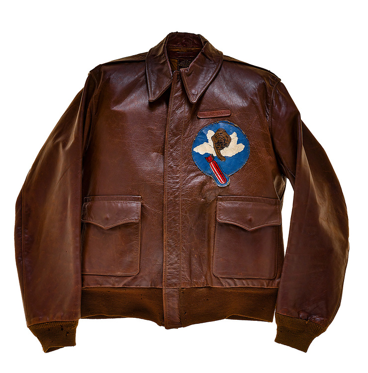 """William T. Dinwiddie, a pilot on """"Gung Ho"""", wore this type A2 flight jacket. Dinwiddie and his crew were attached to the 569th squadron of the 390th Bomb Group. The 569th squadron insignia patch, a bear dropping a bomb from the clouds, is attached to the front of the jacket. Above the squadron patch is the name plate which reads """"W.T. Dinwiddie"""". The name """"Gung Ho"""" is painted on the back of the jacket with a yellow machine gun between the two words. Each bomb painted on the jacket represents a successful mission flown by Dinwiddie and his crew. """"Gung Ho"""" completed 101 missions before being shot down on its 102nd mission. This was the third most missions by an aircraft in the 390th bombardment group."""