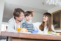 Family at breakfast table, smiling
