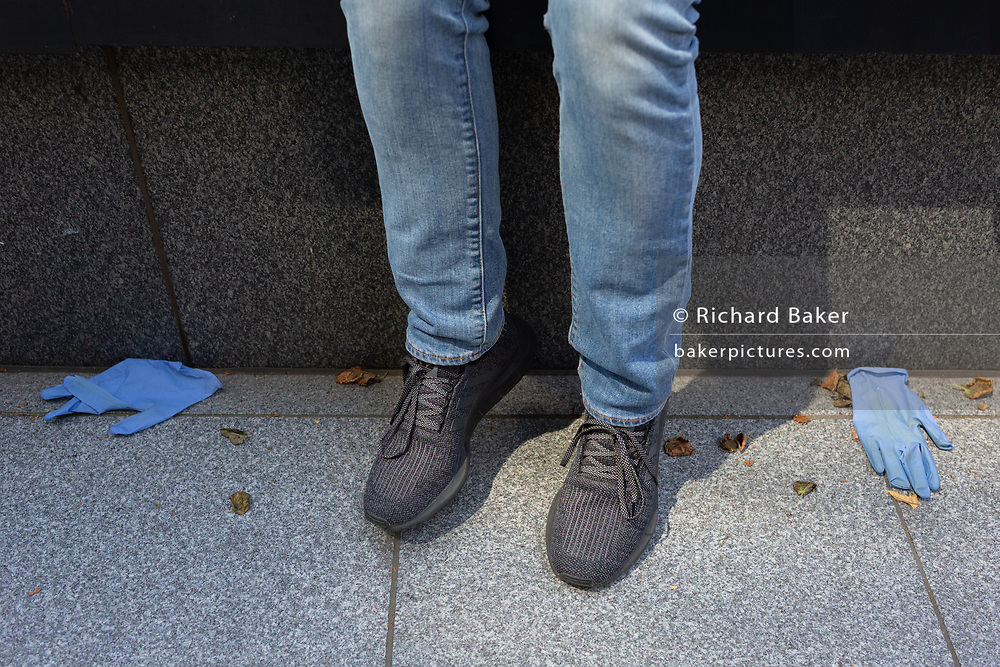 A close-up of a pair of lower legs and shoes with a pair of discarded protecting gloves on the ground in the City of London during the Coronavirus pandemic, on 31st July 2020, in London, England.