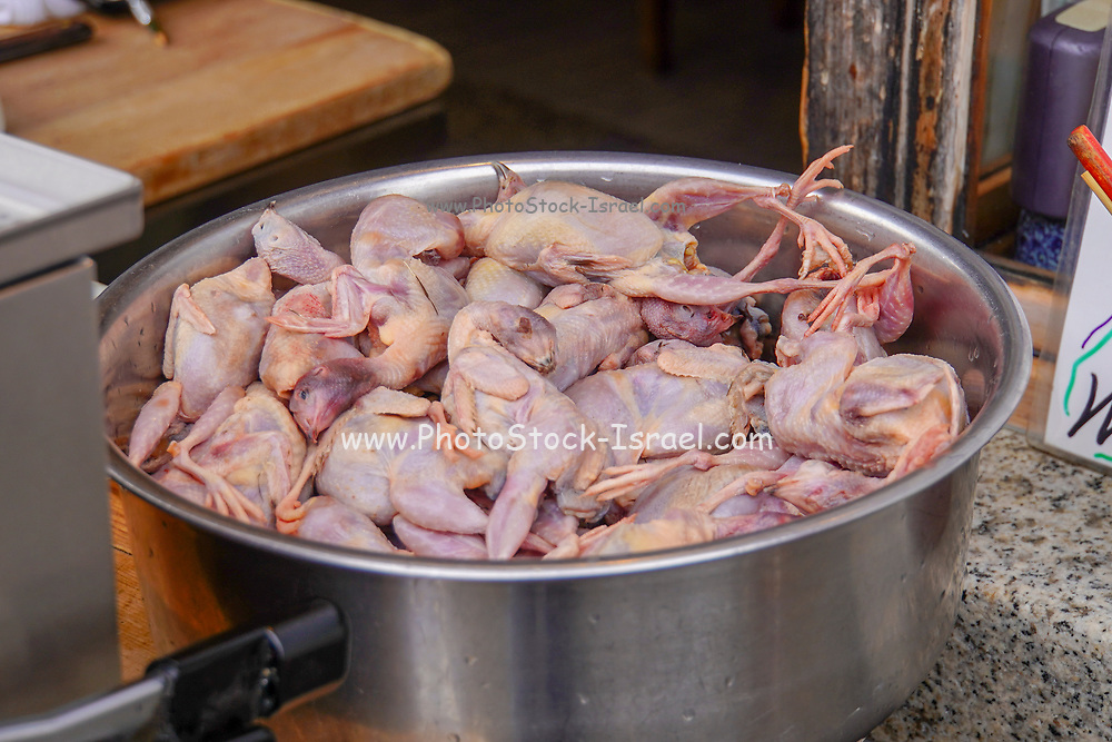 Whole plucked chickens with heads in a large pot, ready for cooking. Photographed at the Fushimi Inari Taisha Shrine, Kyoto, Japan