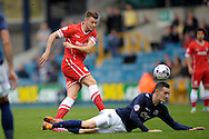 Anthony Pilkington of Cardiff City has a shot at goal deflected by Shaun Williams of Millwall. Skybet football league championship match , Millwall v Cardiff city at the Den in Millwall, London on Saturday 25th October 2014.<br /> pic by John Patrick Fletcher, Andrew Orchard sports photography.