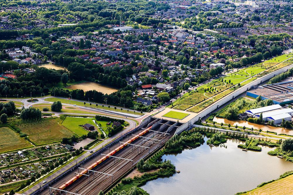 Nederland, Zuid-Holland, Barendrecht, 15-07-2012; een goederentrein die rijdt op de Betuweroute verlaat de Overkapping Barendrecht. Op het dak van de overkapping is o.a. een vlinderpark aangelegd. De constructie is gebouwd over 9 spoorlijnen, waaronder naast de Betuweroute de HSL en dient om geluidsoverlast tegen te gaan. .The railway station is part of the covering-over of the HST in Barendrecht (SW Netherlands)  . Roof landscape has a parking lot and a butterfly garden. A freight train is just passing by. luchtfoto (toeslag), aerial photo (additional fee required).foto/photo Siebe Swart